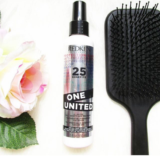 Redken One United Leave In Conditioner junto a un cepillo plano y una rosa